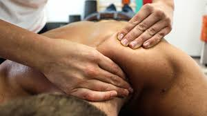 Pro massage therapist providing back massage in shoulder area for the client
