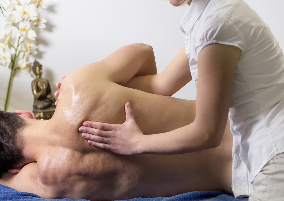 Pro massage therapist providing shoulder therapy technique by placing the client on his side