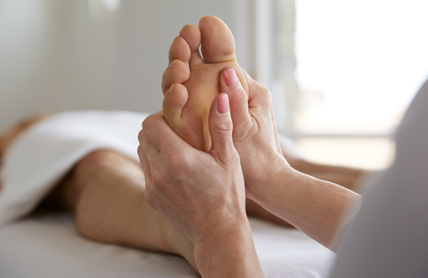 Pro massage therapist providing upper foot pressure for