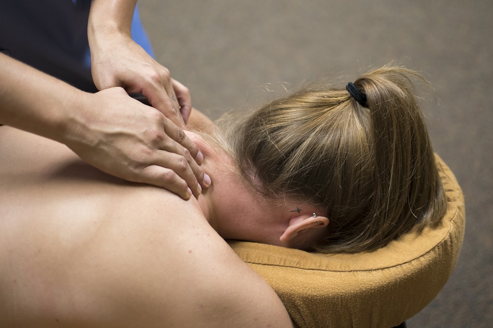 Pro massage therapist providing neck and shoulder for female client